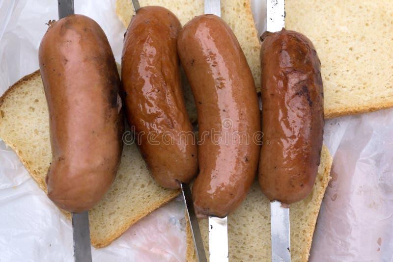 Gegrillte Wurst auf einem glühenden Grill mit Brot lizenzfreies stockbild