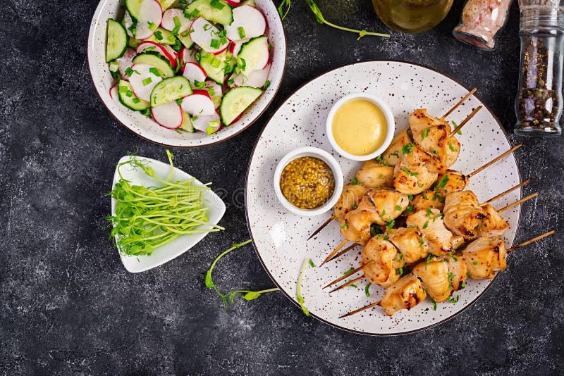 Gegrillter Hühnerkebab und -salat mit Gurke, Rettich, Zwiebel lizenzfreies stockbild