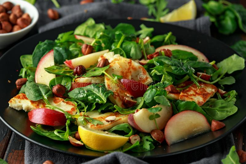 Gegrillter Halloumi-Käsesalat mit Pfirsichfrucht, Nüssen und Spinat, Arugulamischung Gesunde Nahrung nahaufnahme stockfoto