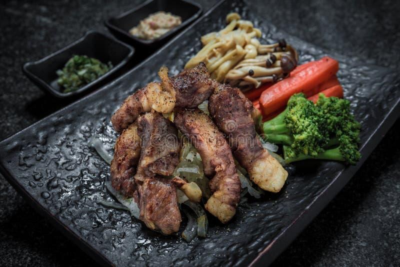 Gegrillter japanischer Lebensmittelschnitt des Fleisches auf dem Schwarzblechaufschlag mit Gemüse lizenzfreie stockfotografie