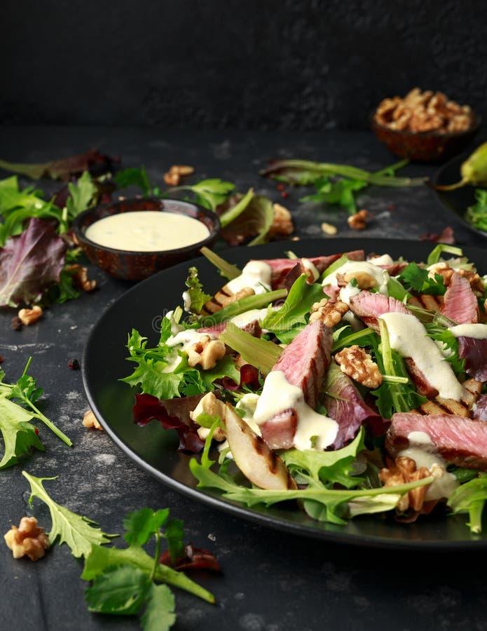 Gegrillter Rindfleisch-Steaksalat mit Birnen, Waln?sse und Gr?ngem?se und Blauschimmelk?seso?e Gesunde Nahrung stockfotos
