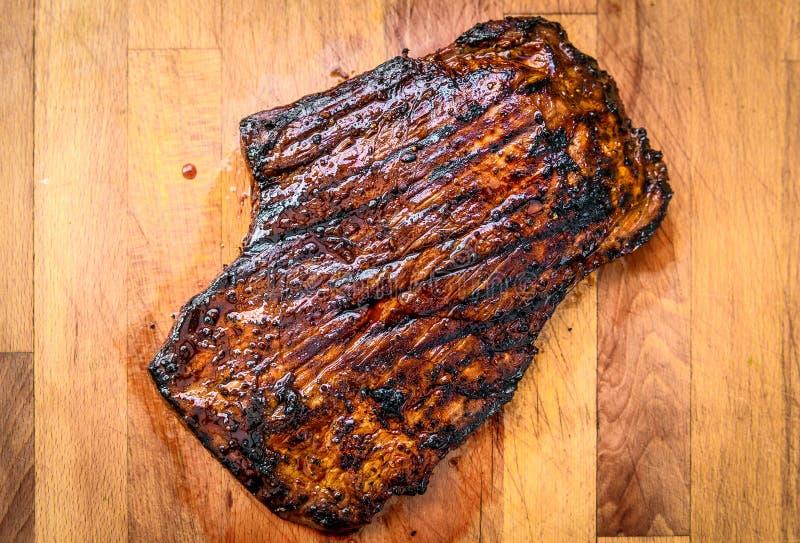 Gegrillter saftiger marinierter Rindfleischbauchlappen auf hölzernem Brett stockfotos