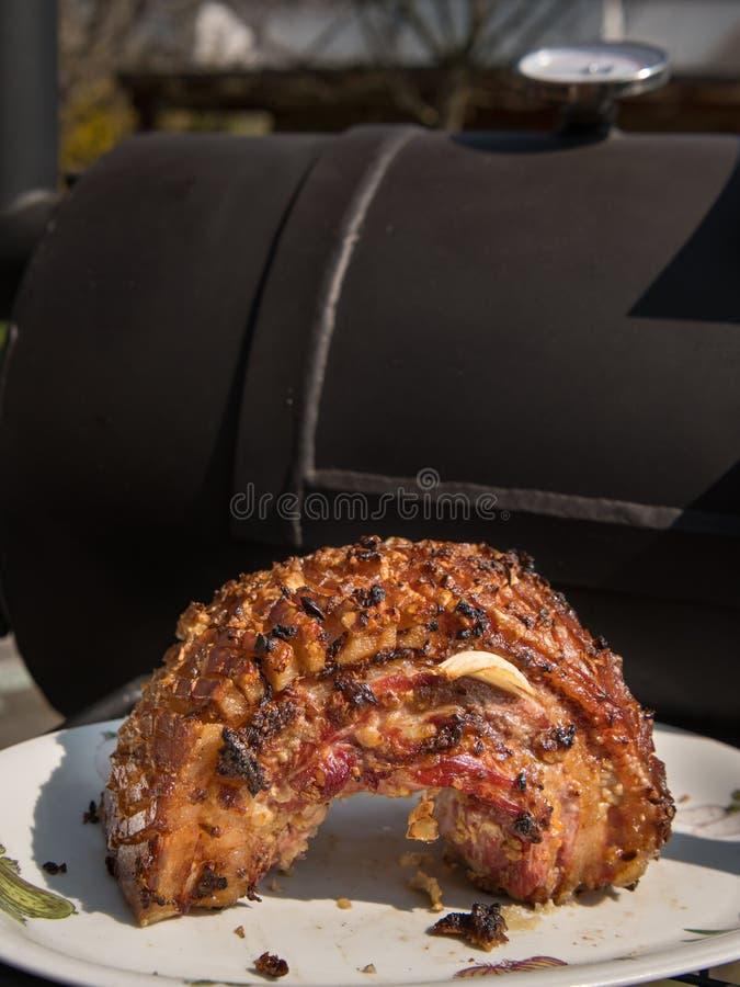 Gegrillter Schweinebauch vor einem BBQ-Raucher stockfoto
