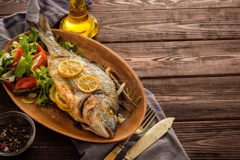 Gegrilltes Dorado mit Zitrone, Thymian, Rosmarin und frischem Salat auf Th stockfoto