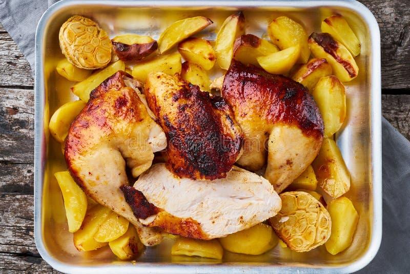 Gegrilltes Hühnerfleisch, Bein, Schenkel mit Ofenkartoffeln, Knoblauch Draufsicht, Abschluss oben Grauer alter Holztisch stockfoto