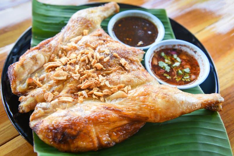 Gegrilltes Huhn mit Knoblauch und würziger Soße auf Platte - asiatische thailändische Artnahrung grillte Hühnerganzen Körper stockfotografie