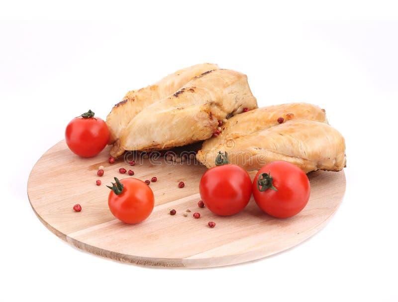 Gegrilltes Huhn mit Tomaten auf hölzerner Servierplatte stockbild