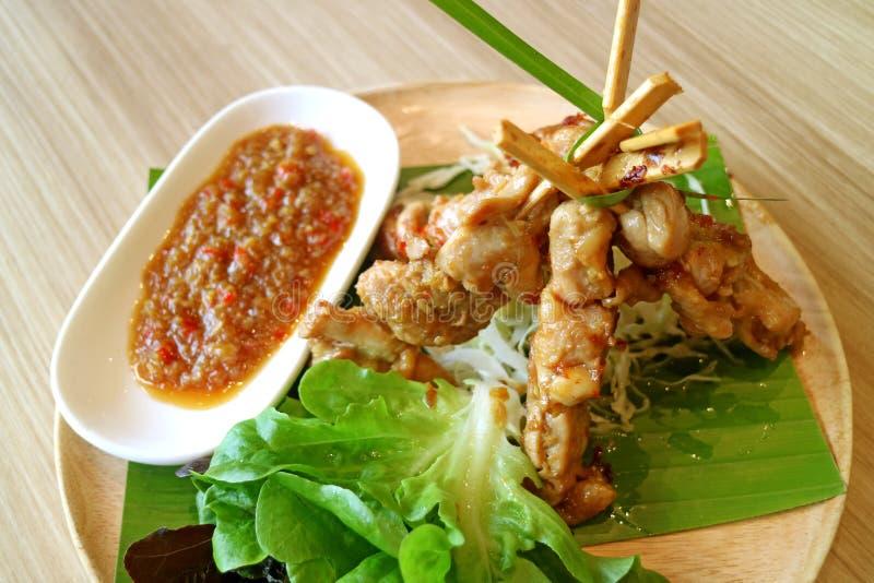 Gegrilltes Huhn mit würziger Soße und grünen dem Salat gedient auf hölzerner Platte stockbild