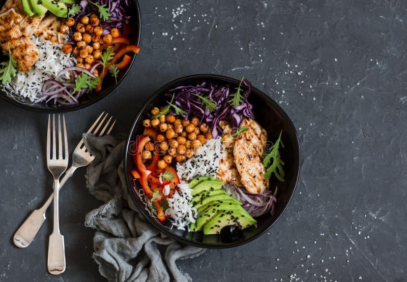 Gegrilltes Huhn, Reis, würzige Kichererbsen, Avocado, Kohl, Pfefferbuddha-Schüssel auf dunklem Hintergrund, Draufsicht stockbild