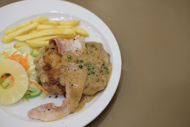 Gegrilltes Huhn und Speck mit Soße des schwarzen Pfeffers, Karotte lizenzfreies stockbild