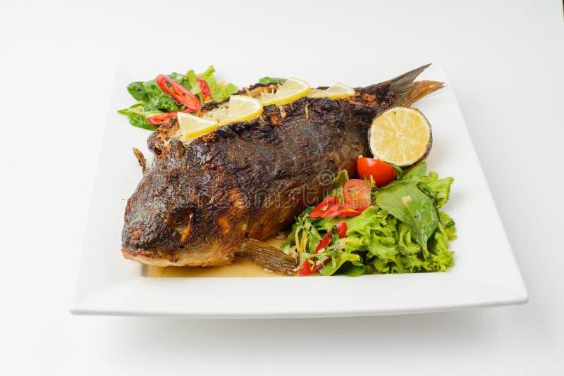 Gegrilltes Lachssteak mit Gemüse auf Platte auf Weiß stockfoto