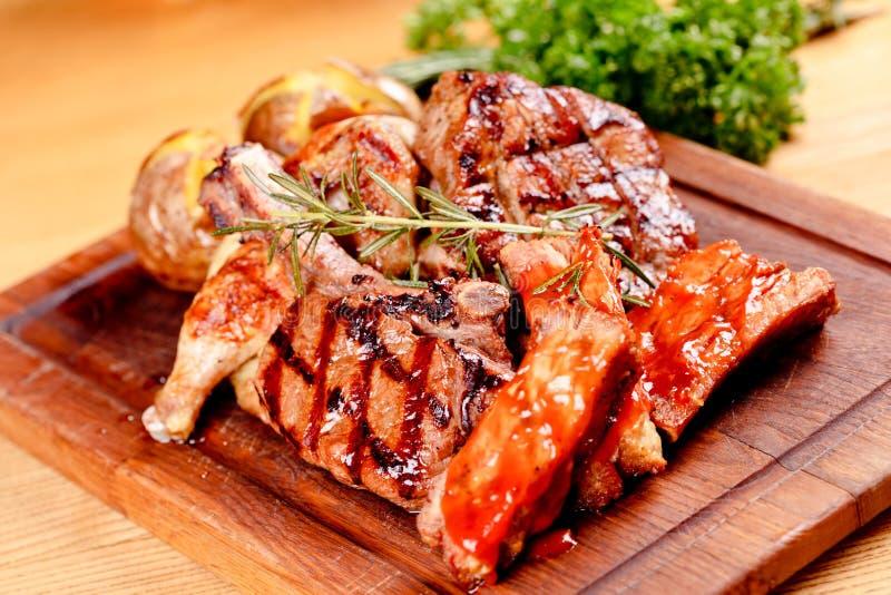 Gegrilltes Mischfleisch und Kartoffel auf hölzernem Schneidebrett Schweinefleisch, Rindfleisch, Geflügel stockfotografie