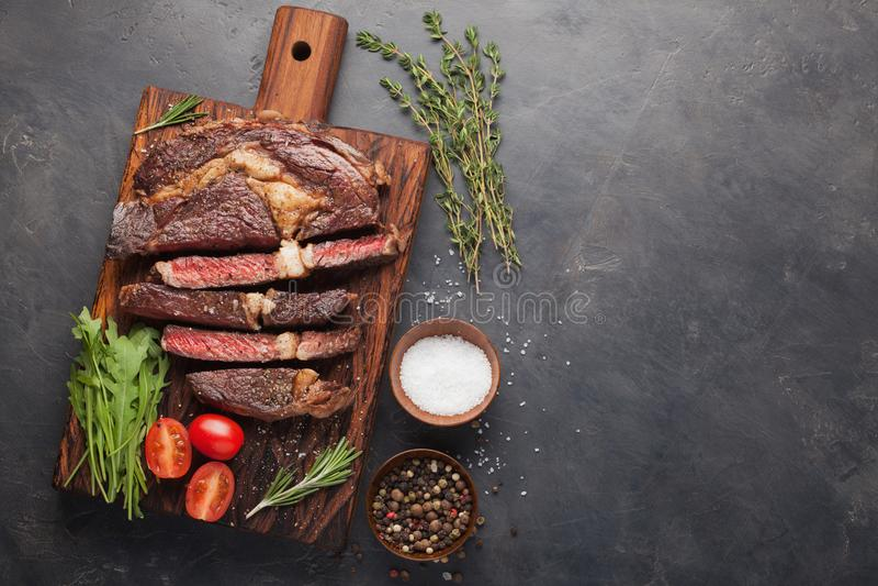 Gegrilltes ribeye Rindfleischsteak mit Rotwein, Kräutern und Gewürzen auf einem dunklen Steinhintergrund Draufsicht mit Kopienrau lizenzfreie stockfotografie