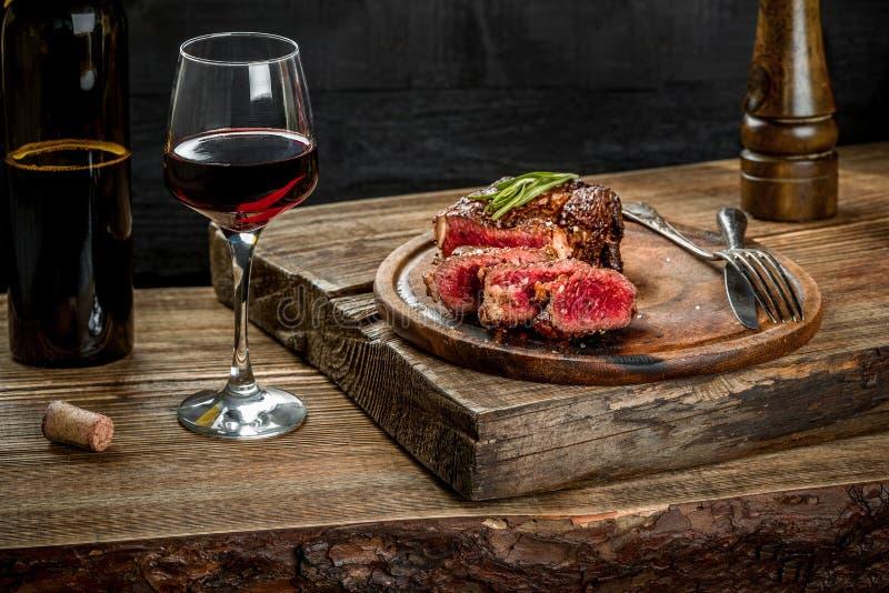 Gegrilltes ribeye Rindfleischsteak mit Rotwein, Kräutern und Gewürzen auf Holztisch lizenzfreies stockfoto