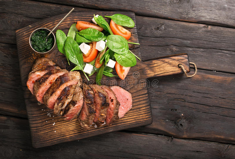 Gegrilltes Rindfleischgrill Striploin-Steak, Salat und chimichurri sau lizenzfreie stockfotos