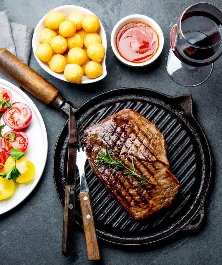 Gegrilltes Rindfleischsteak auf Grillwanne diente mit Tomatensalat, Kartoffelbällen und Wein Grill, bbq-FleischRindsfilet stockbild