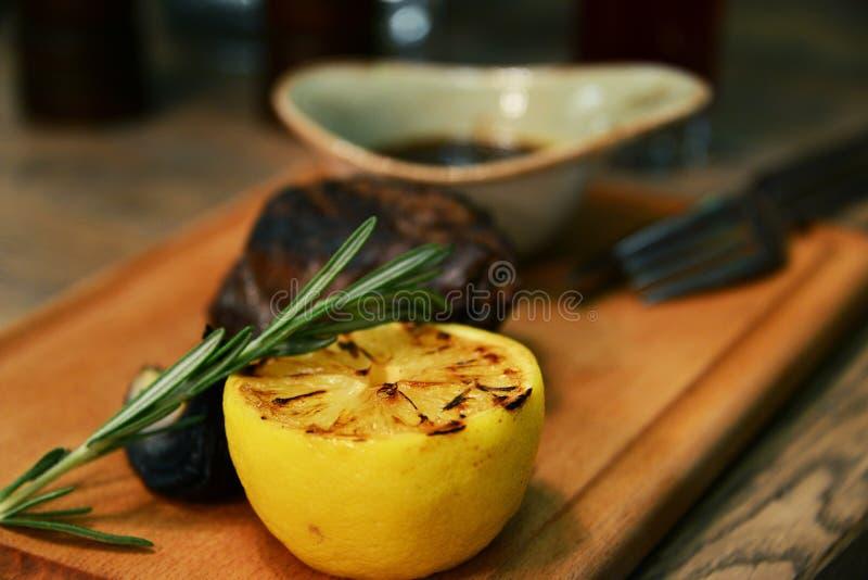 Gegrilltes Rindfleischsteak und -hälfte rösteten Zitrone auf einem hölzernen Brett stockfoto