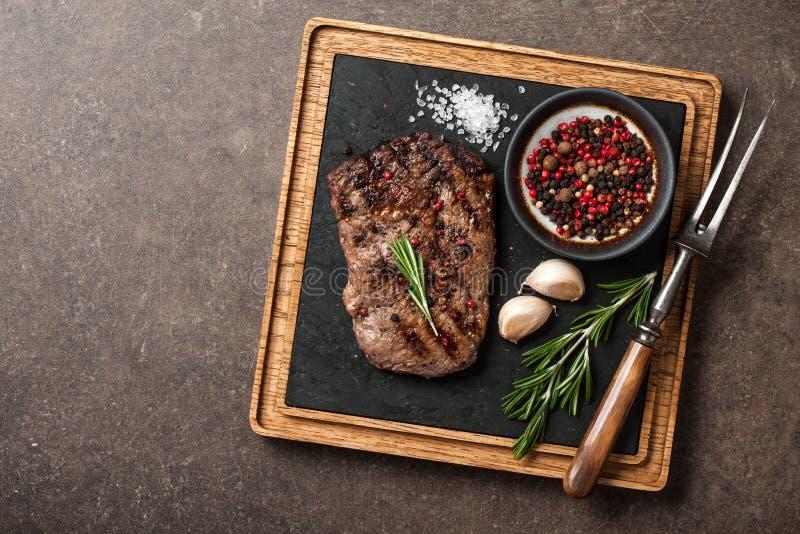 Gegrilltes Rippenaugensteak, Gewürze und Weinlesefleisch gabelt auf dem Dienen von b lizenzfreie stockfotografie