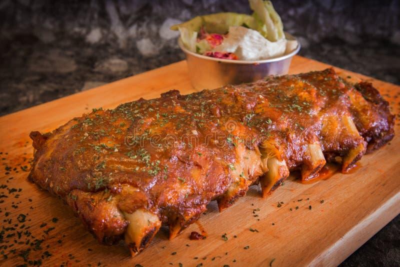 Gegrilltes Rippenschweinefleisch mit Barbecue-Soße und Gemüse auf hölzernem Schneidebrett stockbild