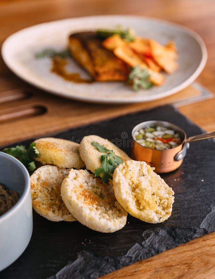 Gegrilltes Schweinefleisch überstiegen mit Koriander und mit einem englischen Muffin, einem in Essig eingelegten Gemüse und zerkr lizenzfreies stockfoto