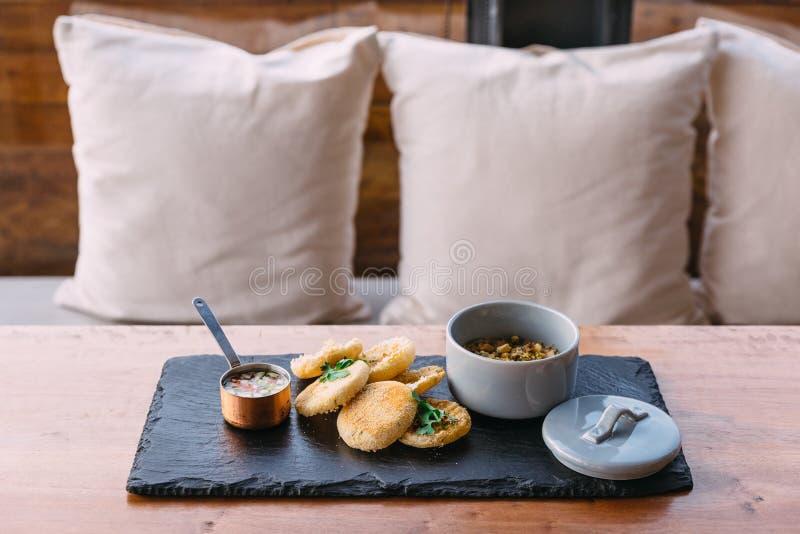 Gegrilltes Schweinefleisch überstiegen mit Koriander und mit einem englischen Muffin, einem in Essig eingelegten Gemüse und zerkr lizenzfreie stockfotografie