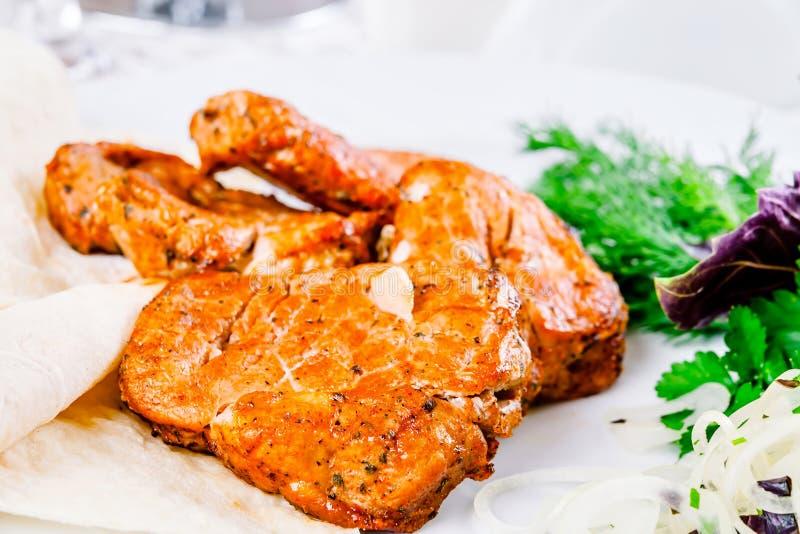 Gegrilltes Schweinefleisch mit Zwiebelringen und -kräutern stockfoto