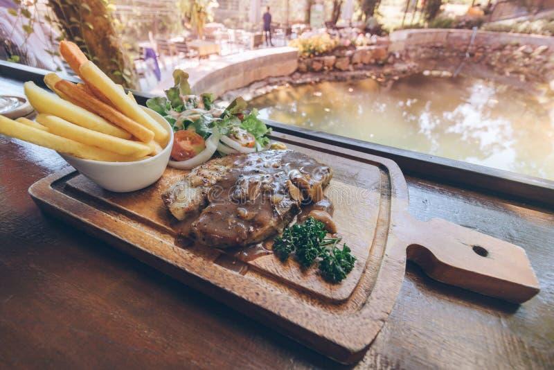 Gegrilltes Schweinefleisch-Steak mit Pommes-Frites, Salat auf hölzerner Platte lizenzfreies stockbild