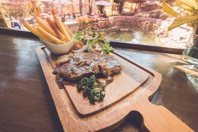 Gegrilltes Schweinefleisch-Steak mit Pommes-Frites, Salat auf hölzerner Platte lizenzfreie stockfotos