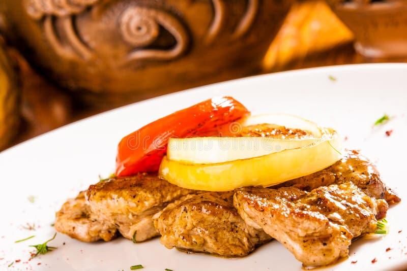 Gegrilltes Schweinefleischsteak mit Zwiebelringen und Tomatenscheibe lizenzfreies stockbild