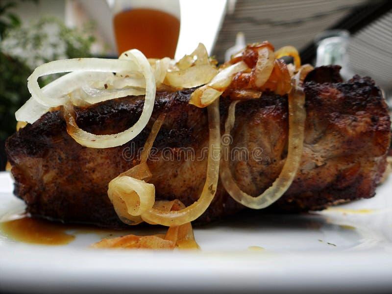 Gegrilltes Schweinekotelett mit Zwiebeln, Brot und Gurke lizenzfreies stockfoto