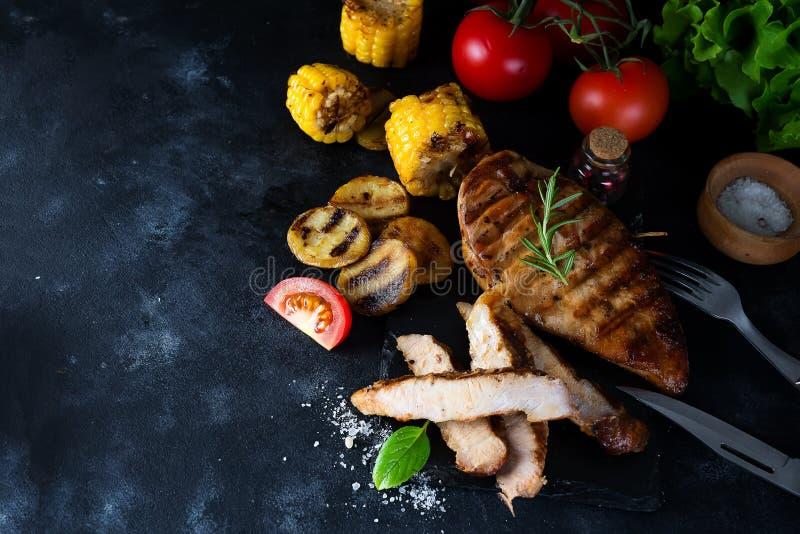 Gegrilltes Steak und Gemüse, Ofenkartoffeln und grüner Salat auf Dunkelheit stockbilder