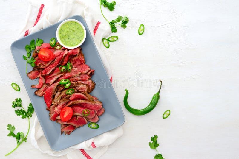 Gegrilltes und geschnittenes seltenes Rindfleischrocksteak diente mit grünem chimi lizenzfreie stockbilder