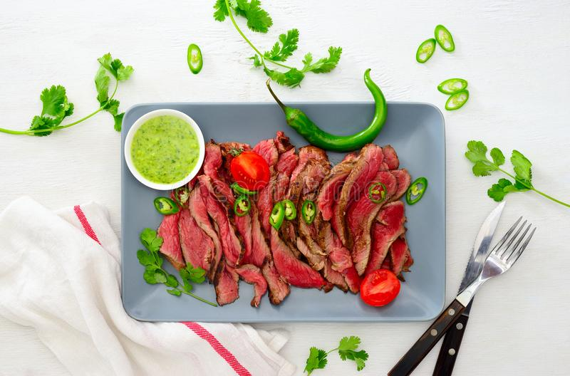 Gegrilltes und geschnittenes seltenes Rindfleischrocksteak diente mit grünem chimi stockfotografie