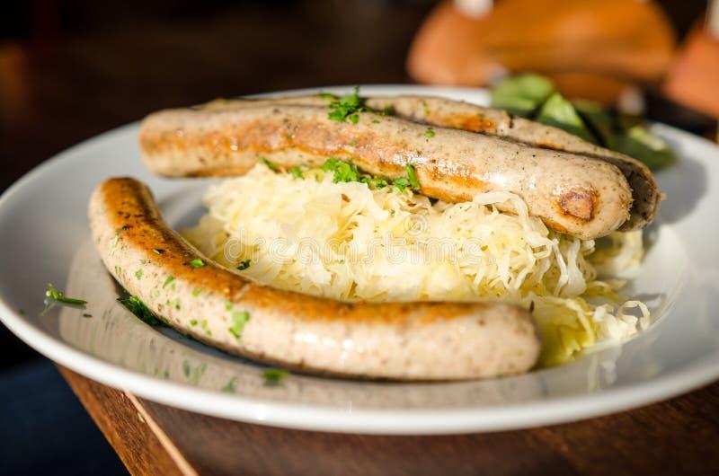 Gegrilltes Weisswurst mit Sauerkraut lizenzfreie stockfotografie
