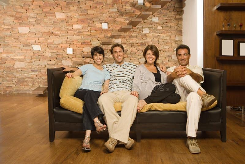 Gegroeide familie op de bank stock afbeeldingen