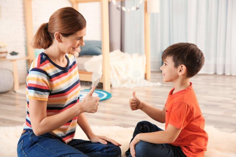 Gehörgeschädigte Mutter und ihr Kind, die mithilfe der Gebärdensprache spricht lizenzfreie stockfotografie
