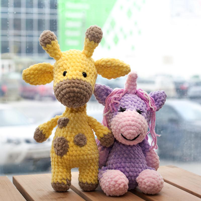 Gehaakte amigurumi gele giraf en eenhoorn Gebreid met de hand gemaakt stuk speelgoed stock foto
