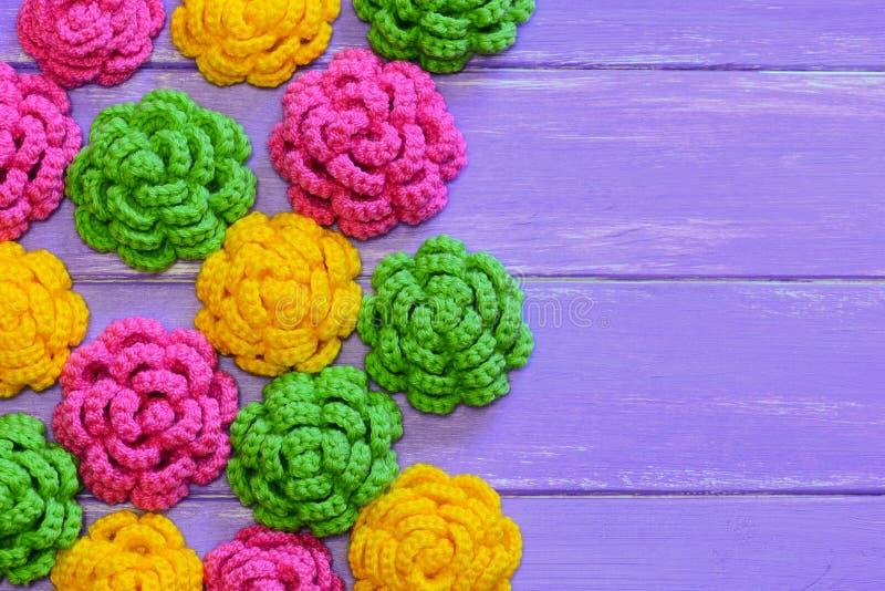 Gehaakte rozen Gele, roze en groene gehaakte rozen Kleurrijke bloemendecoratie op een houten achtergrond met exemplaarruimte royalty-vrije stock afbeeldingen
