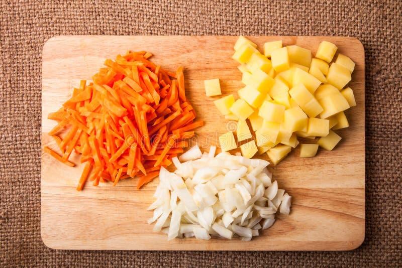 Gehackte Zwiebeln, Karotten, Kartoffeln gestapelt in den Gruppen auf einem hölzernen stockfotografie