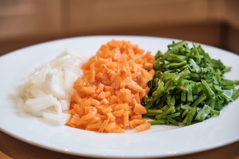 Gehackte Zwiebeln, Karotten und Bohnen auf einer Platte stockbild