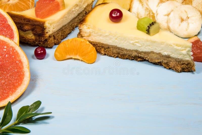 Gehackter Käsekuchen auf einem blauen Holztisch mit Frucht und Zitrusfrucht stockfotografie
