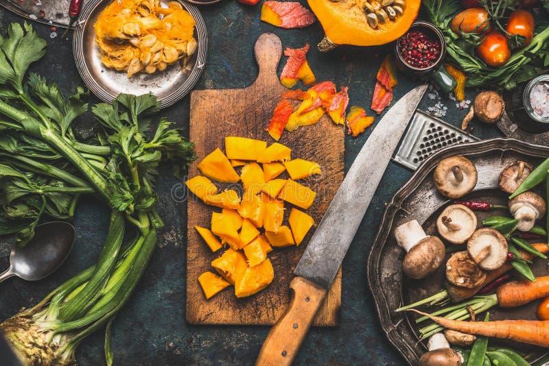 Gehackter Kürbis auf rustikalem Schneidebrett mit Küchenmesser und Pilze und Gemüsebestandteile für das geschmackvolle vegetarisc stockfotografie