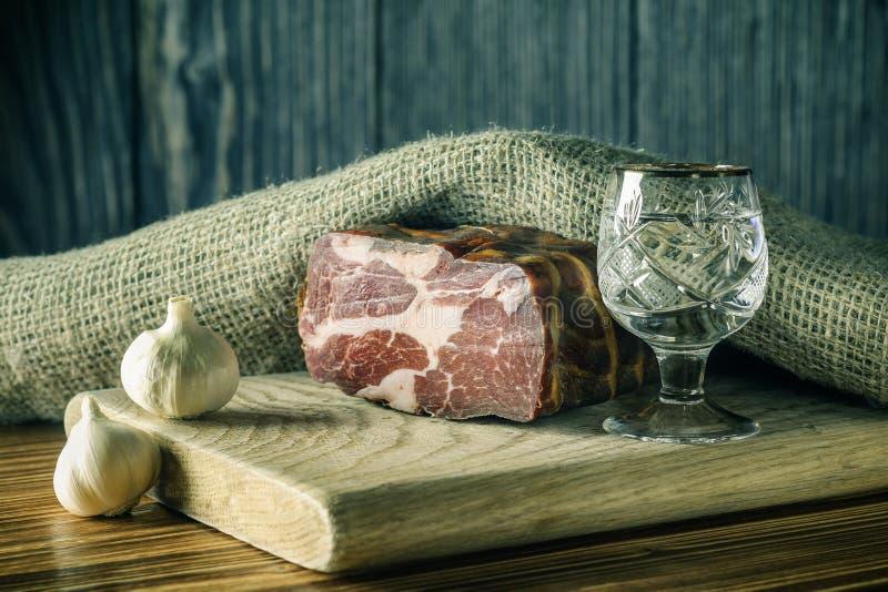 Gehakt stuk van droog vlees met knoflook en een drank van wodka op een scherpe raad Stilleven 1 royalty-vrije stock foto's