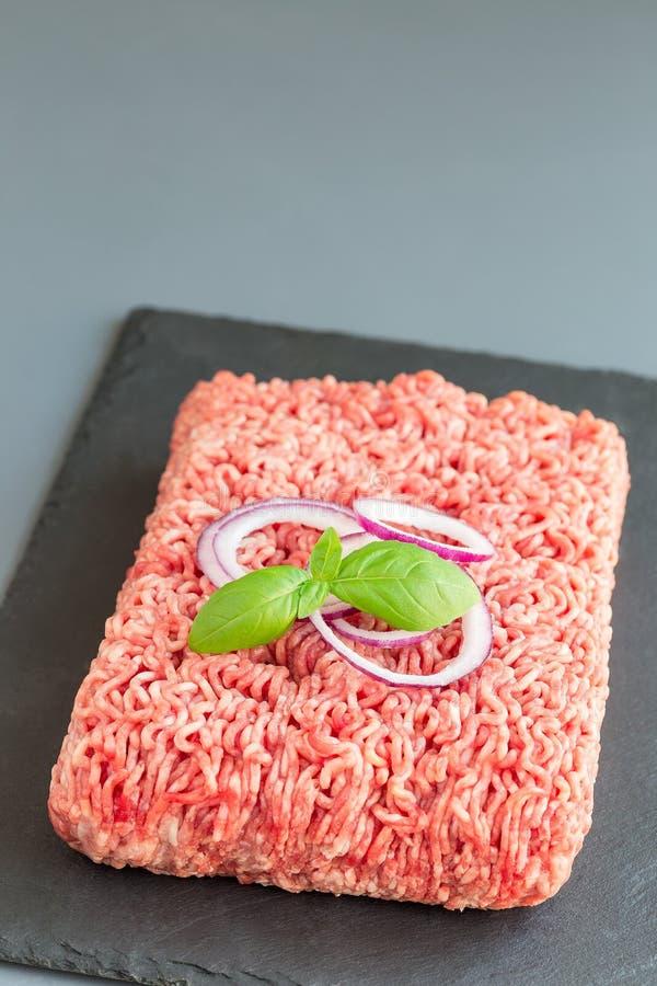 Gehakt van varkensvlees en rundvlees, gehakt op donkere leiraad, verticaal, exemplaarruimte stock afbeelding