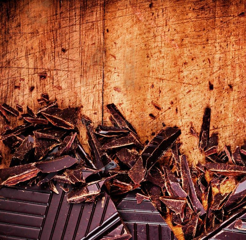 Gehakte Chocoladereep op houten close-up als achtergrond. Gebroken dark stock fotografie