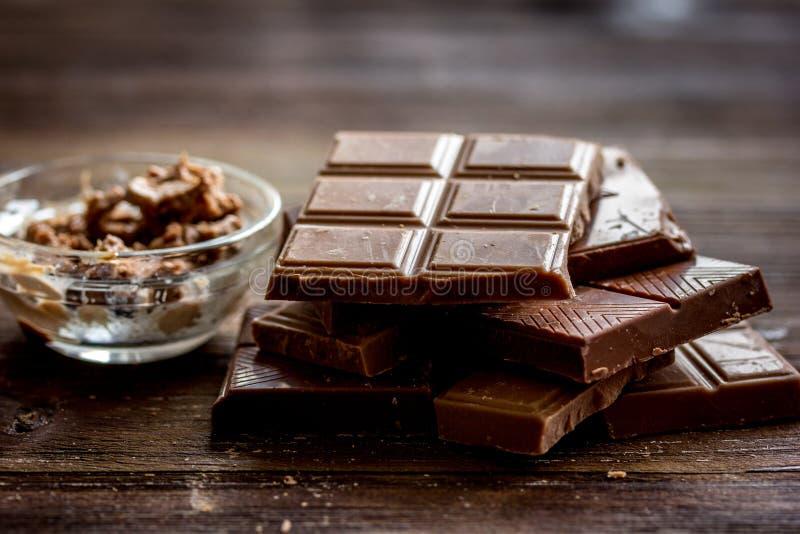 Gehakte chocoladestukken voor achtergrond van het dessert de donkere houten bureau stock foto's