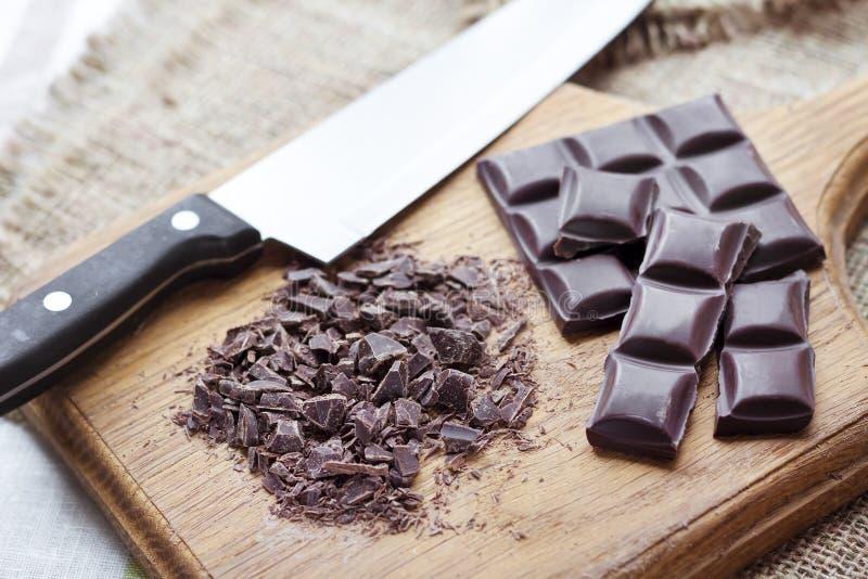 Gehakte donkere chocolade op scherpe raad stock afbeelding