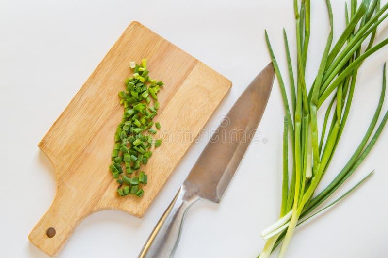 Gehakte groene ui op houten Raad, mes op wit geïsoleerde achtergrond, gezond natuurvoedingconcept royalty-vrije stock foto's