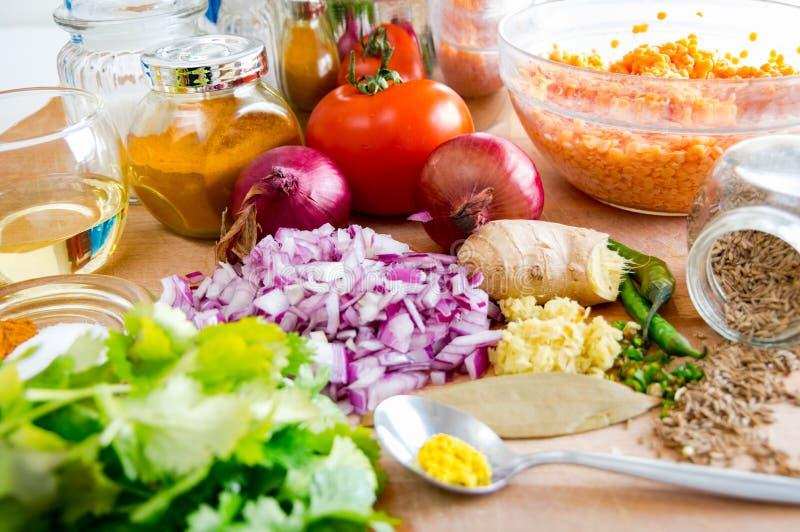 Gehakte groenten en kruiden op een houten keukenlijst stock foto