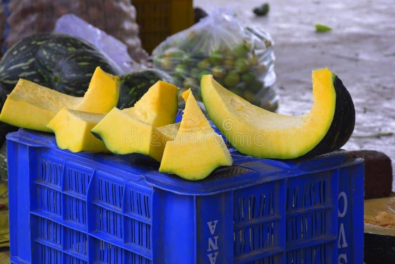 Gehakte pompoenstukken en pompoen op blauw karaat, gereed voor verkoop op de wegmarkt royalty-vrije stock afbeelding